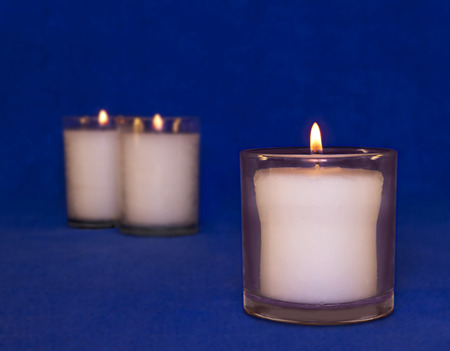 shul: Group memorial yahrzeit candles.  Jewish custom is to light a candle on the anniversary of death of a loved one and on religious holidays.  Typically used is a thick white wax candle in a glass jar.  Soft blurred textured dark blue background  Stock Photo