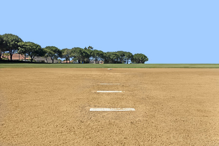 pitching: Amateur baseball field in public park   View from infield pitching rubber toward second base  Grass outfield and trees background  Blue sky