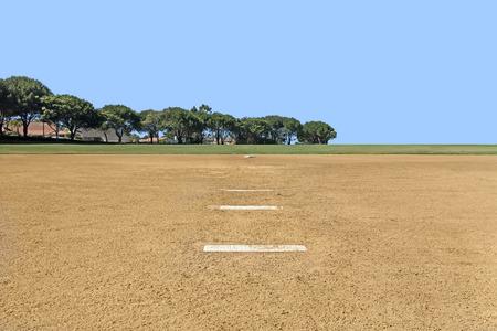 suelo arenoso: Campo de béisbol amateur en el parque público de Vista desde goma de lanzar infield hacia outfield hierba segunda base y los árboles de fondo azul cielo