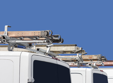 utility: Row of home repair contractor vans and ladders   Rear view of white utility truck with metal ladder on vehicle roof. Blue sky background. Stock Photo