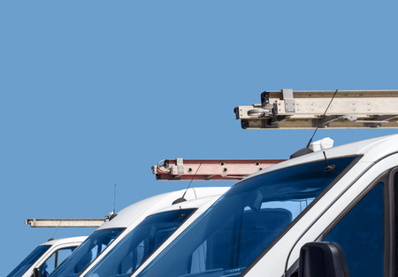 utility: Row of home repair contractor vans and ladders   Front view of white utility trucks with metal ladders on vehicle roof. Blue sky background. Room for text, copy space. Stock Photo