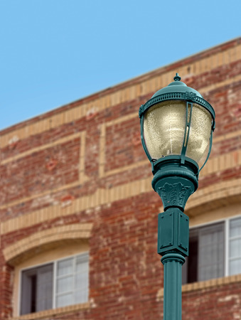 metal post: Vintage design electrical streetlamp with red brick building background   Old fashioned style lit lantern with metal post. Bulb inside glass cover. Blue sky.