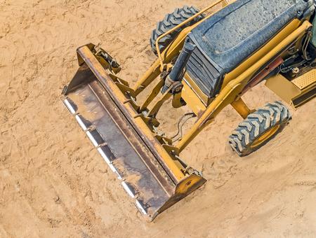 suelo arenoso: Amarillo vehículo cargador construcción estacionado en suelo arenoso arriba hacia abajo vista de cubo, neumáticos, la banda de rodadura del neumático.