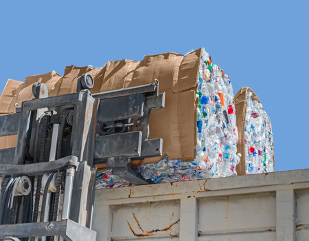 water recycling: Plastic bottle recycling   Industrial machine crane with stack of empty crushed plastic drinking containers in cardboard box and large metal dumpster.  Stock Photo