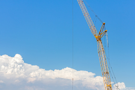 Industrial heavy equipment tower crane above the clouds   Center part of metal frame structure with rope hanging down. Blue sky and clouds background. Room for text, copy space. photo