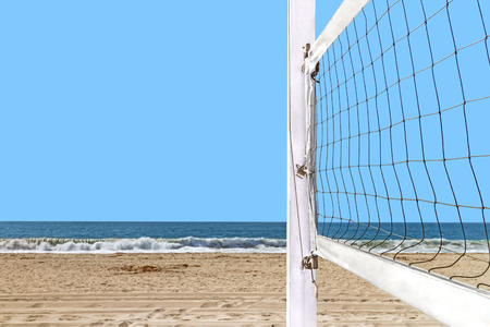 Close up of beach volleyball net mounted on wood post   Sand, ocean waves, blue sky background. Room for text, copy space. photo