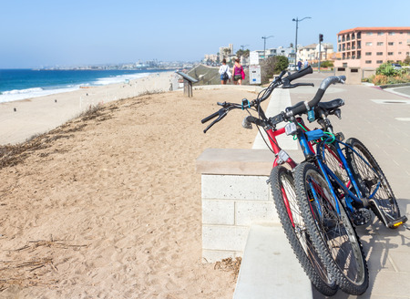 knobby: Two bicycles parked on paved sidewalk overlooking a suburban beach in Southern California   Front view of bike handlebars and knobby tires. Ocean, sand, sky, people, buildings in background.