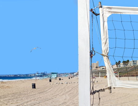 Close up of beach volleyball net mounted on wood post at suburban beach in Southern California   Sand, ocean, bird flying, buildings and blue sky in background. Room for text, copy space. photo