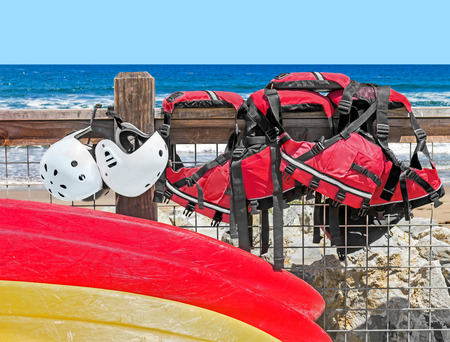 safety gear: Yellow and red kayaks and kayaking protective gear   Safety equipment helmets and life jackets on wood fence. Blue ocean water and sky background. Stock Photo