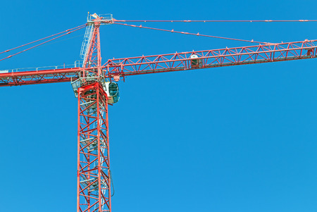 Industrial tower crane against clear blue sky   Center part of metal frame structure showing operator photo