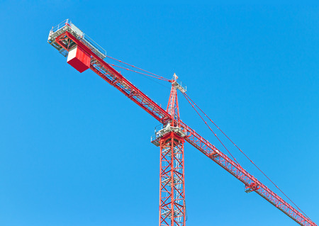 counterweight: Construction industry tower crane against clear blue sky   Heavy metal frame structure showing counterweight and counterjib.
