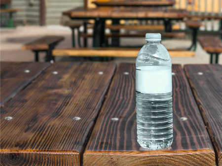 eating area: Clear plastic water bottle on outdoor wood picnic table   Outside eating area with row of rustic wooden tables.