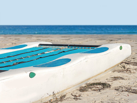 beached: Close up rear view of beached white and blue kayak on the sand   Ocean and blue sky background. Room for text, copyspace.
