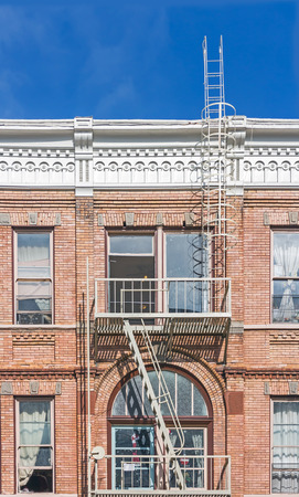 evacuate: Fire escape on exterior of old Victorian style building    Red brick residential building with white painted metal outdoor staircase, landing, and ladder going up to the roof for fire safety.