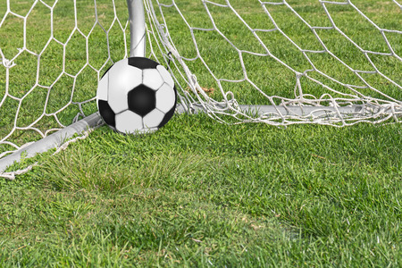 Black and white soccer ball in net corner on grass    Success or winning concept. photo