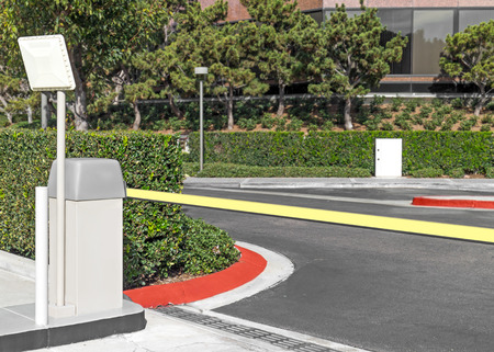 parking station: Suburban outdoor parking lot exit blocked by pay station gate arm