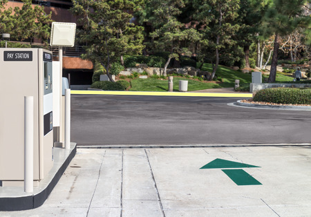 Suburban outdoor parking lot driveway exit blocked by pay station gate arm   photo