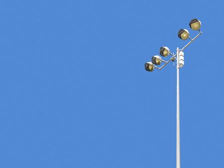 Outdoor stadium lights against daytime blue sky   Single row of bulbs on tall metal pole. photo