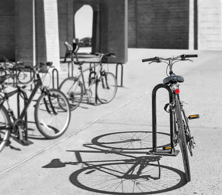 Rear view of bicycle locked to metal u shaped bike rack with hard shadow   Be different or stand alone concept. photo