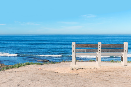 cliff top: Empty wood bench on cliff top overlooking the ocean   Rolling waves. Blue sky, horizon view. Room for text, copyspace.