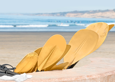 black white kayak: Group of sandy yellow kayak paddles at the beach   Paddle blade resting on cement wall with black sandal and white towel. Stock Photo