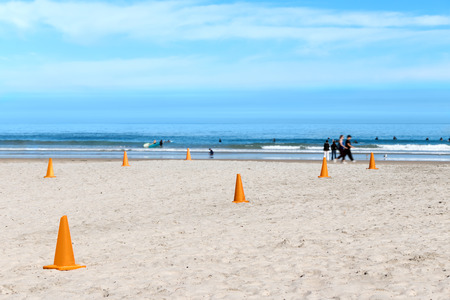safe water: Rows of plastic orange safety cones on sandy beach showing where it is safe to swim or surf   Blurred background with people walking on sand, surfers in the water. Blue ocean, cloudy sky. Stock Photo