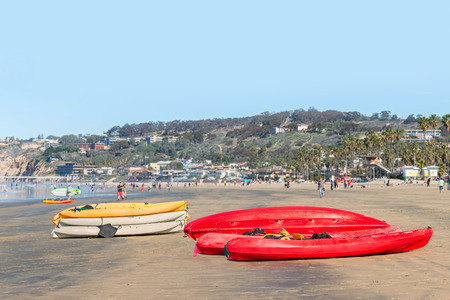 Group of red white and yellow kayaks stacked on a busy suburban beach   People, buildings, and hill in blurred background. photo