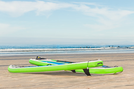 paddleboard: Pair of bright green stand up paddleboards with black fins on sandy beach by the ocean   Overcast sky. Background with people surfboarding in the waves. Room for text, copy space. Stock Photo