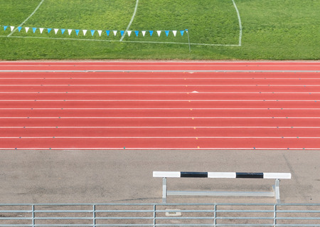 steeplechase: Side view of multi lane athletic running track and field with black and white steeplechase hurdle on the side   Metal fence in foreground. Hanging banner, white lines over grass in blurred background. View from above. Stock Photo