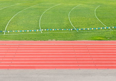 lane lines: Side view of multi lane athletic running track and field    Hanging banner and curved white lines over grass. View from above.