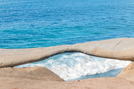 foamy: Looking at foamy ocean wave through eye shape rock formation  Lots of blue water. Room for text, copy space. Stock Photo