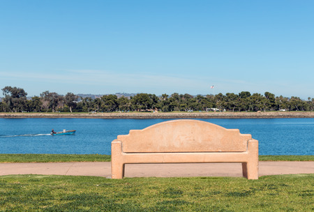 paved: Empty stone bench on paved walkway overlooking the river   Grassy area in foreground. Person in motorboat moving through the water in the background. Leisure and relaxation concept. Stock Photo