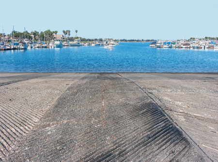 traction: Concrete boat ramp going down into the water on the marina   Rough texture asphalt for traction. Blue water and sky in blurred background. Wide angle perspective view.