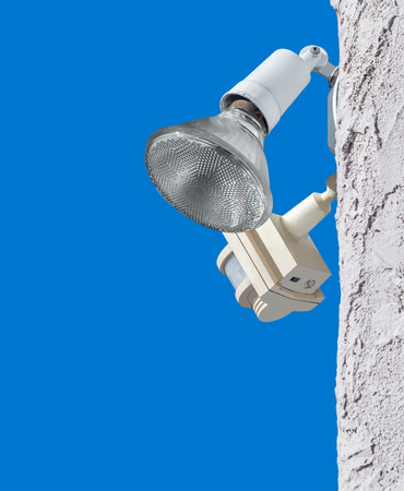 motion sensor: Outdoor home security light and motion sensor on white stucco wall   Residential security adjustable position lamp bulb and detector. Blue sky background.