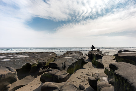 high contrast: Rock formations on the beach at low tide overlooking the ocean waves   Backlit, high contrast scene, wide angle view. Silhouette of man sitting in chair in the distance. Stock Photo