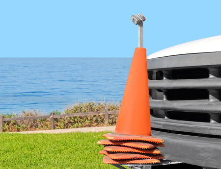 Stacked orange traffic cones mounted on truck front bumper parked near the ocean   Secured and locked on a metal pole with a padlock. Outdoor repair and maintenance concept. Green grass, blue water and sky background. photo