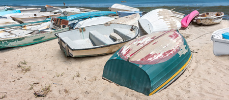 dinghies: Old small boats on sandy beach   Weathered and dirty dinghies scattered across the sand. Stock Photo