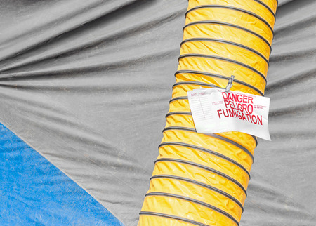 fumigation: Home fumigation tarp and yellow duct, danger sign in English and Spanish   Close up detail of heavy canvas material, flexible ducting, red and white warning notice. Stock Photo