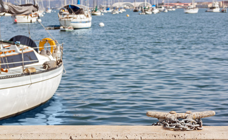 cleat: Boat cleat on stone surface with heavy metal anchor chain.   Motorboats yachts and calm blue water in blurred background. Room for text. Copy space. Stock Photo