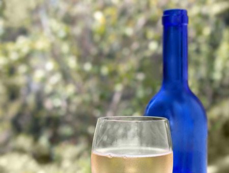 bubbly: Glass of chilled bubbly white wine.   Festive outdoor dining concept. Water drop condensation on glass. Blue bottle in blurred green and yellow bokeh background.