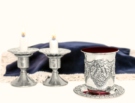 sabbath: Shabbat silver kiddush cup overflowing with red wine.    Lit candles and covered challah in blurred background. Room for text. Copy space. Isolated on white.