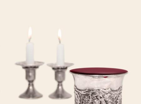 shabat: Shabat copa de kidush plata rebosante de vino tinto con velas encendidas. Cierre de vista. Sitio para el texto. Copie el espacio. Objetos aislados. Foto de archivo