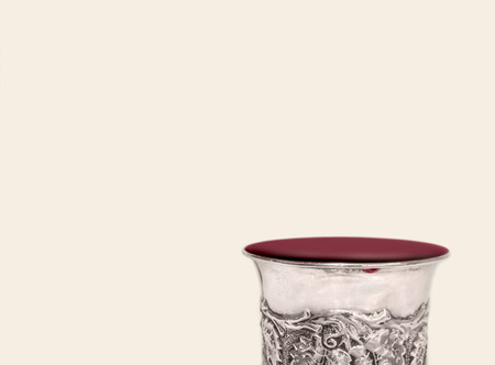 kiddush: Shabbat silver kiddush cup overflowing with red wine close up.   Room for text. Copy space. Isolated object.