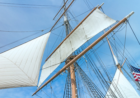 Windjammer tall ship with mast sail and rigging .   Vintage sailing ship blue sky and cloudy background. photo