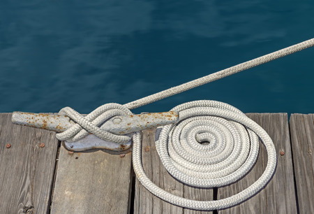 wooden boat: Coiled white cloth boat rope tied to rusty metal cleat on wood plank dock   This type of nautical knot called a cleat hitch is a secure way to tie a rope to a cleat. Close up view.