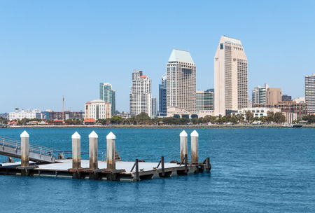 Small floating boat dock with San Diego harbor and skyline background   Clear blue sky offers room for text. Copy space. photo