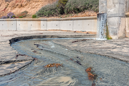 runoff: Hillside storm drain runoff on sandy beach   Flowing water makes a wet path in the sand.