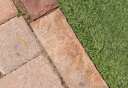 grass close up: Brick walkway edge and grass close up   Rectangle shape paving stones touch blades of green grass Stock Photo