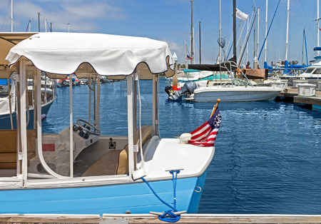 motorboats: Small pleasure boat with white canopy docked in marina   Flag with anchor. Motorboats blue water and sky background. Stock Photo