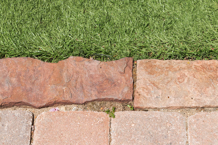 uneven edge: Uneven brick walkway edge and grass close up   Rectangle shape paving stones touch blades of green grass